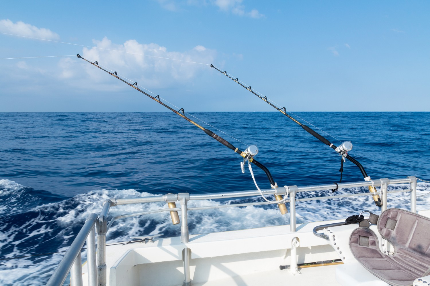 Sport fishing with two salt water rods and reels. Deep sea fishing in the ocean on a sunny blue sky day with fluffy clouds.