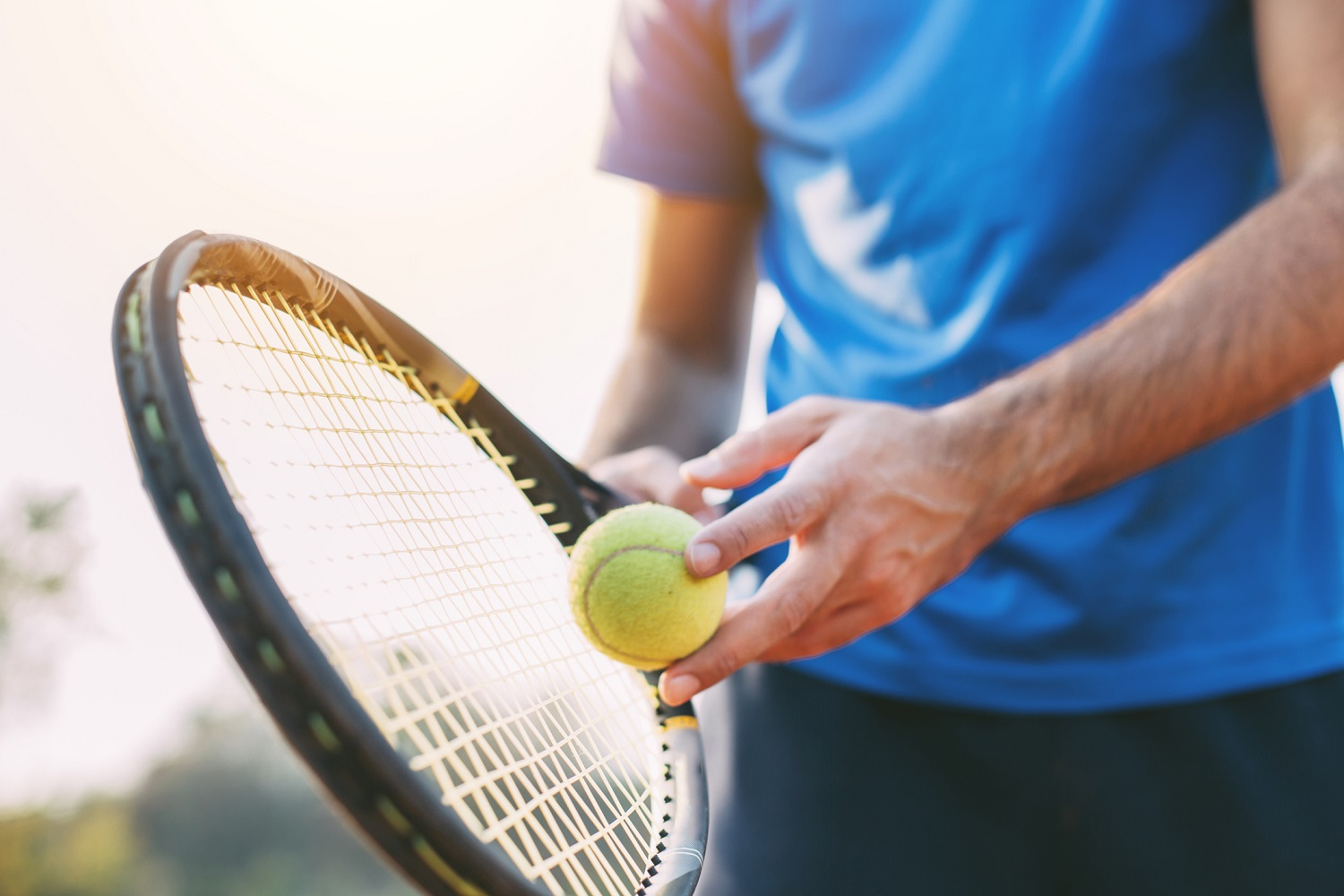 Guy holding tennis racket and ball on clay court. Boy getting ready for a serve in tennis.
