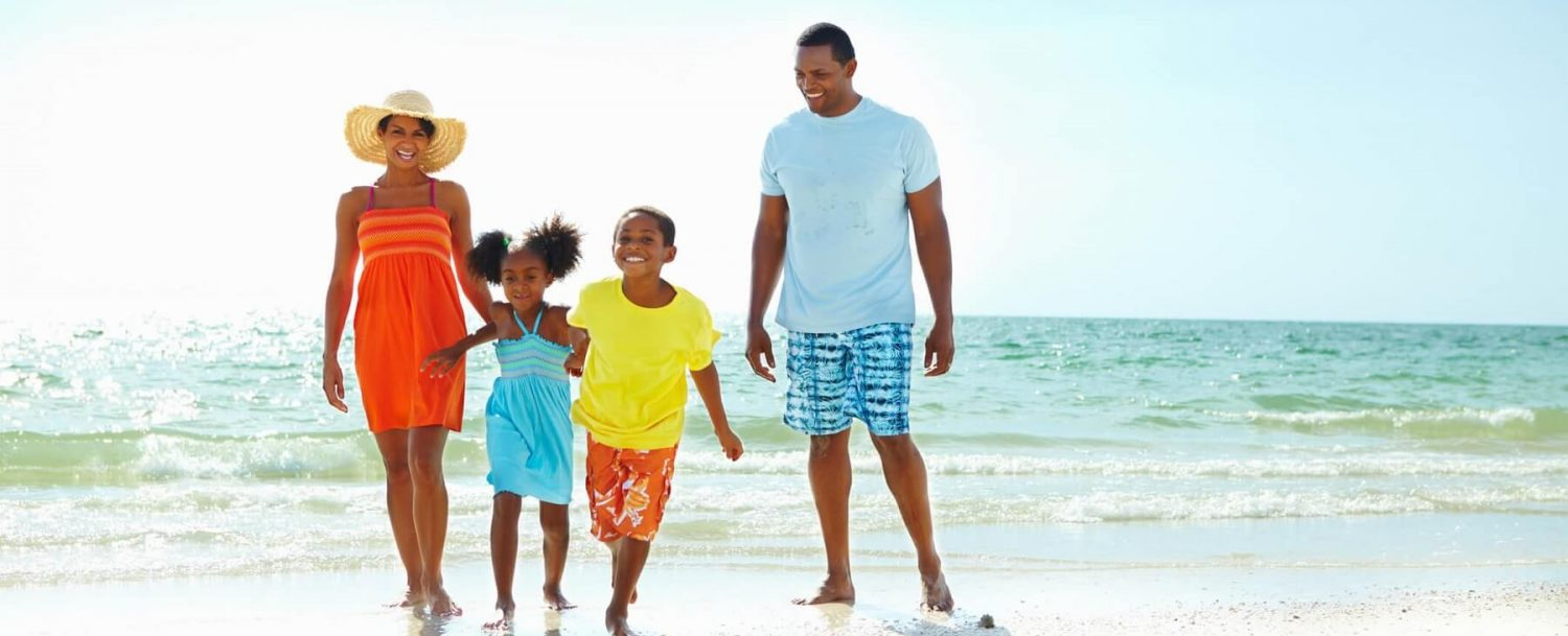 family of four at the beach laughing