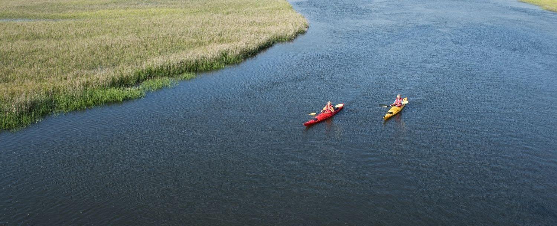 Two paddlers enjoying Fripp Island kayaking through the marsh