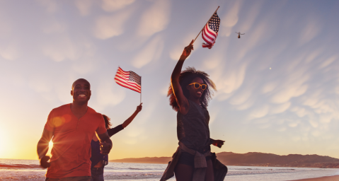 Friends running on the beach waving American flags for Memorial Day